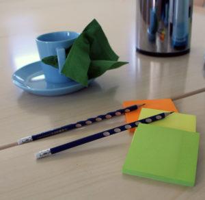 Kahvikuppi, post-it-lappu ja kynät